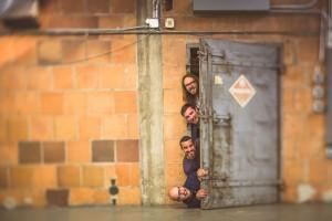The Modist team sticking their heads through a metal warehouse door